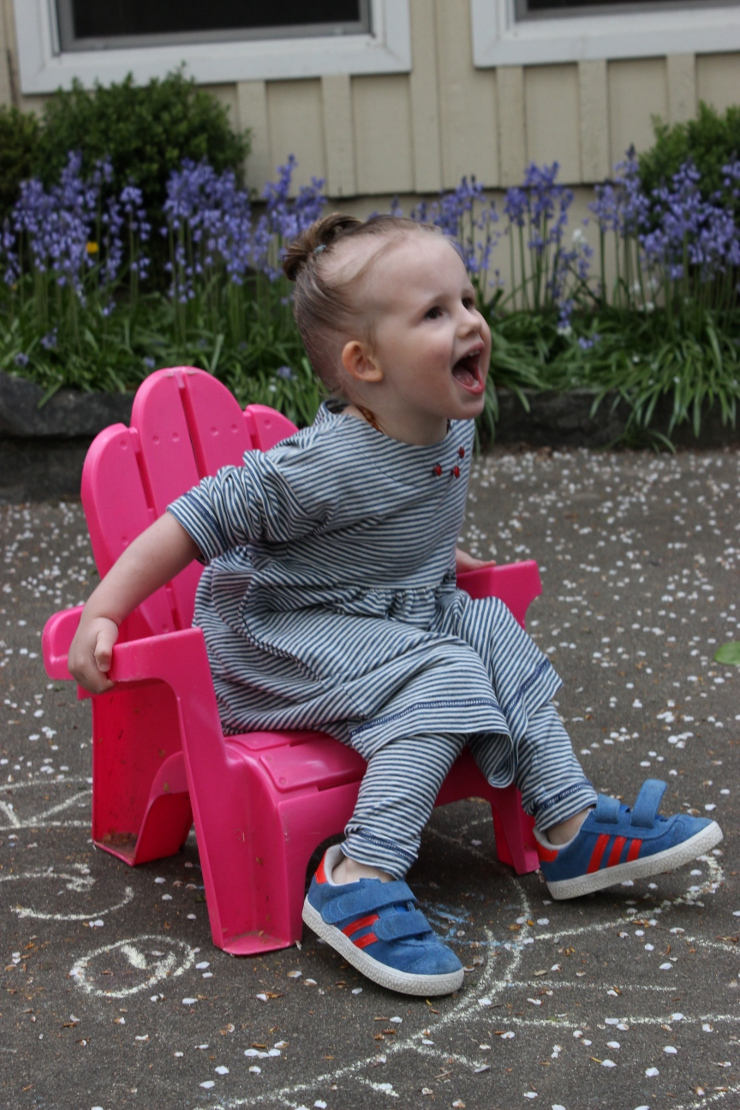 Toddler wearing Playtime dress by Sew Maris and sitting in toddler chair